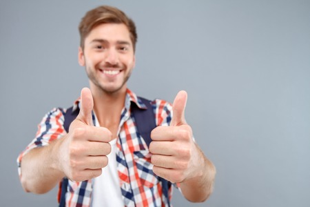 laugher: Think positively. Nice euphoric young student thumbing up and expressing gladness while standing isolated on grey background. Stock Photo