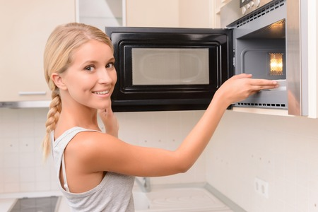 vivacious: Healthy lifestyle. Vivacious positive young woman opening oven and touching plate while enjoying cooking