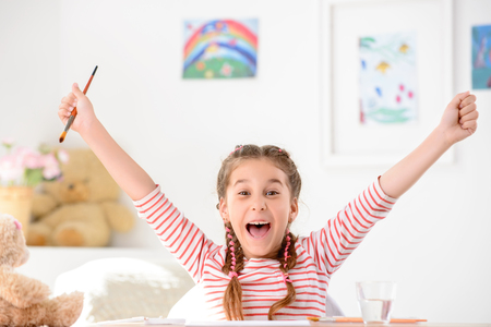 laugher: On the edge of joy. Delighted little girl holding her hands up and holding painting brush while feeling completely happy Stock Photo