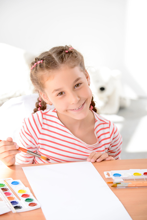 laugher: Do you want to help. Top view of pleasant smiling little girl holding brush and looking up while enjoying painting.