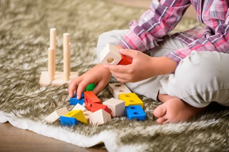 laugher: Open happiness. Close up of hands of little boy playing with colorful cubes on the carpet while sitting on the floor. Stock Photo