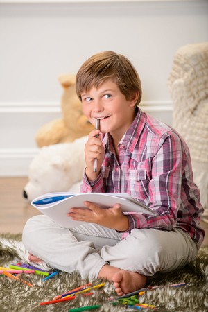 contented: Let me think. Pleasant contented little boy sitting on the carpet and holding album with pen while thinking
