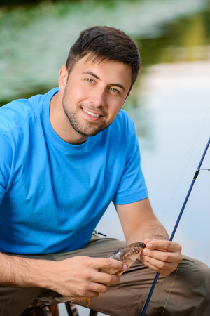 contented: Like fishing. Pleasant contented smiling man holding fish and rod while expressing positivity