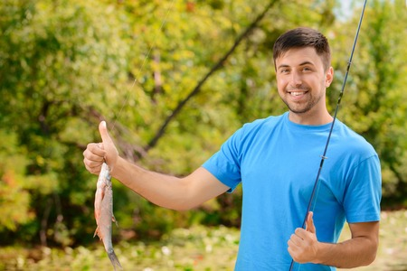 upbeat: Full of energy. Nice positive upbeat man holding rod and thumbing up while having big fish