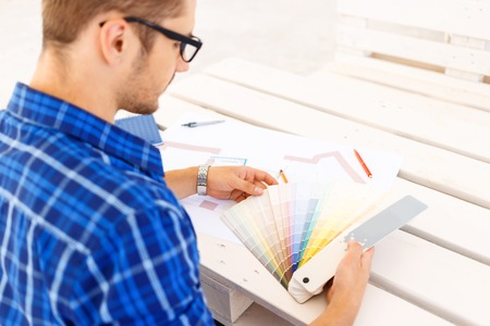 diligente: ¿Qué elegir. Diligente buen trabajador alegre celebración de un conjunto de colores y escogiendo la opción mientras se está sentado en la mesa