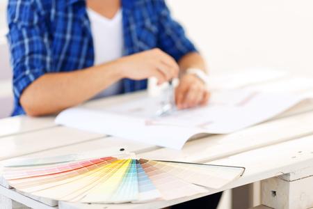 diligente: Freelancer profesional. Conjunto de colores sobre la mesa con el trabajador diligente en el fondo que se sientan en la mesa y haciendo dibujo