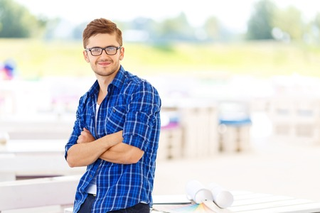 upbeat: Confidence in mind.  Nice upbeat smiling freelancer folding his hands and expressing gladness while standing near table Stock Photo