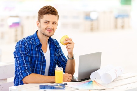 upbeat: Feeling healthy. Nice positive upbeat freelancer sitting at the table and working on the computer while holding apple Stock Photo