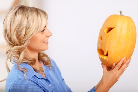 elated: Peace of art. Pretty cheerful happy woman holding pumpkin and looking at it while feeling elated Stock Photo