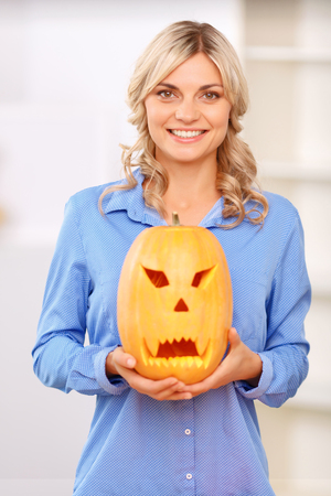 vivacious: Full of positivity, Nice beautiful vivacious woman smiling and holding craved pumpkin while evincing  joy
