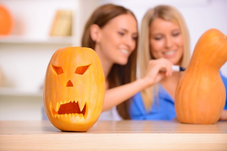 vivacious: Symbol of the celebration. Selective focus of craved pumpkin standing on the table with two nice vivacious  beautiful girls having fun on the background Stock Photo