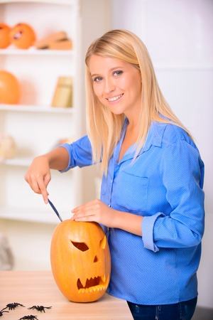 blissful: I am loving it. Pleasant blissful young girl holding knife and craving the pumpkin while expressing gladness. Stock Photo