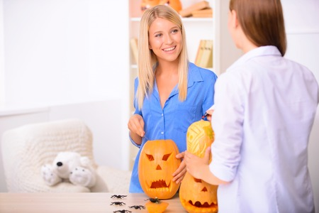 craving: Moment of happiness. Nice  contented smiling girls holding knifes and craving the pumpkins  while having animated conversation.