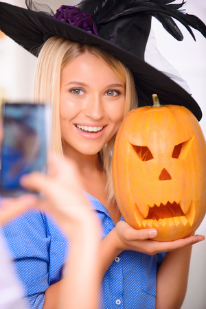 upbeat: Having great time. Pretty charming upbeat girl holding pumpkin and reveling in Halloween party while posing in front of the camera. Stock Photo