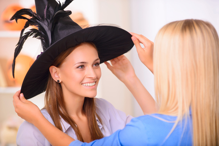 upbeat: I am a witch. Pleasant upbeat girl wearing Halloween hat and expressing positivity while having great time with her friend. Stock Photo