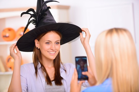 say cheese: Say cheese. Nice positive beautiful girl touching her hat and having Halloween party while posing in front of the camera Stock Photo