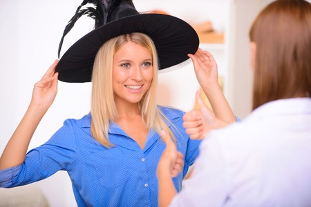 vivacious: Full of positivity. Vivacious nice young girl having Halloween party with her friend and touching her hat while smiling Stock Photo