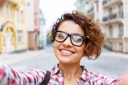 elated: Young and beautiful. Elated pretty girl making selfie while having a walk around the city Stock Photo