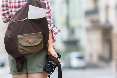 world travel: Ready for new experience. Nice active positive girl holding camera and standing turned back while walking along the street Stock Photo