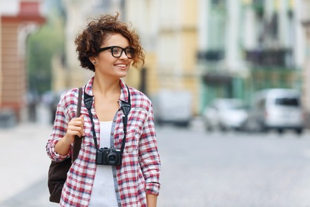 blissful: Happy traveler. Pretty blissful positive girl holding photo camera and expressing gladness while walking around the city