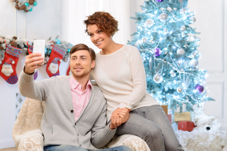elated: Lets make photo. Nice young elated couple sitting in the arm chair and making selfie while feeling overjoyed Stock Photo