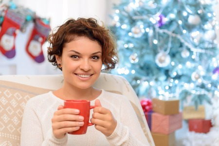 upbeat: Feel the aroma. Pretty young upbeat girl sitting in the arm chair and drinking tea while rejoicing in warm atmosphere Stock Photo