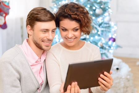 laugher: Feel of positivity. Pleasant young happy couple sitting in the arm chair and holding laptop while feeling overjoyed
