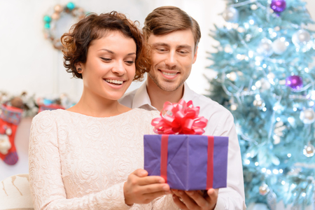 upbeat: What a surprise. Pleasant young upbeat couple standing near Christmas tree and holding present while rejoicing in holiday