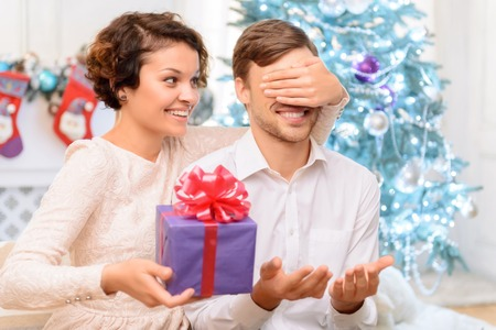 closing eyes: Present for you. Positive cheerful charming girl closing eyes og her boyfriend and going to make surprise for him