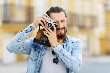 hombre con barba: It is my hobby. Cheerful young bearded handsome man holding camera  and evincing happiness while going to make photos
