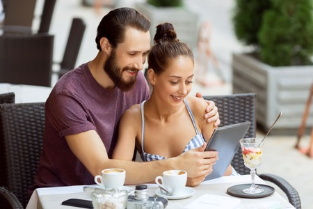 elated: Feeling elated together. Pleasant upbeat young couple sitting at the table and holding laptop while bonding to each other.