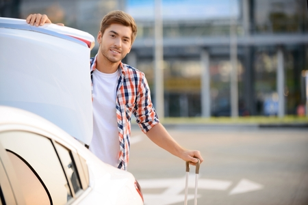 upbeat: Going to ride. Nice positive upbeat boy opening the boot and holding handle while standing near his car