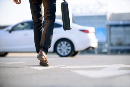 chofer: En el ritmo de los tiempos. Joven hombre de negocios moderna que sostiene caso y va a su coche mientras evidenciando confianza.