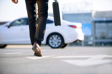 luxuries: In pace of time. Modern young businessman holding case and going to his car while evincing confidence.
