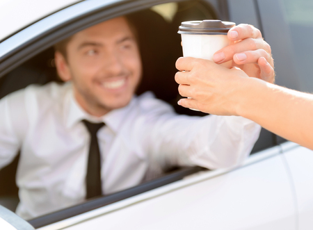 car driving: Here you are. Blissful handsome young businessman driving his car and getting coffee while evincing joy