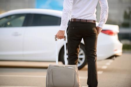 그냥 해외에서. 좋은 현대 사업가 자신의 차가 고 자신감을 evincing하는 동안 가방을 들고.