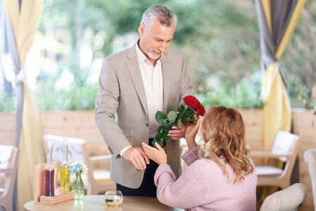 It is for you. Pleasant polite adult gentleman holding bouquet of flowers and presenting it to his wife while having date