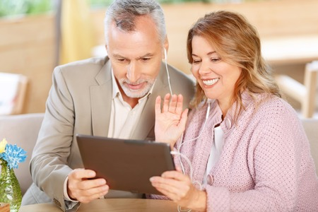 brisk: Brisk conversation. Pleasant cheerful happy adult couple holding laptop and having conversation in Internet while  feeling delighted