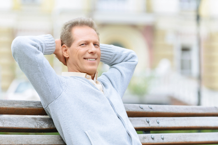True man. Pleasant confident modern man sitting on the bench and drinking coffee while feeling happy