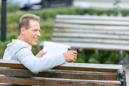 looking aside: Life positive. Nice vivacious adult man sitting on the bench and drinking coffee while looking aside Stock Photo
