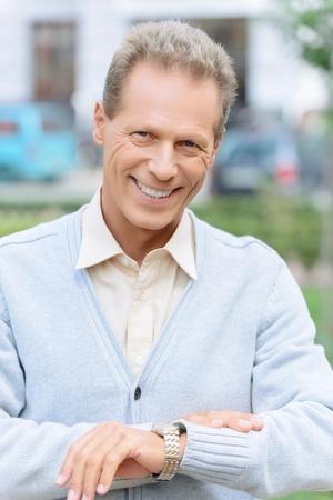 llegar tarde: No llegues tarde. Niza alegre hombre adulto optimista que expresa la positividad y tocar su reloj de pulsera