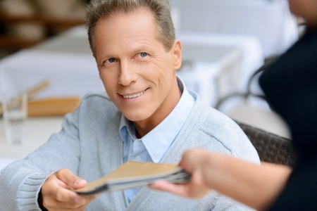 blissful: Here you are. Pleasant  blissful adult man getting the menu and sitting at the table while resting in the cafe Stock Photo