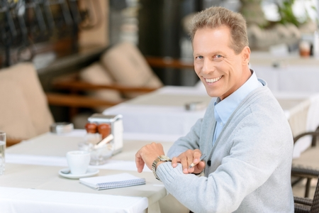 upbeat: What time is it. Cheerful upbeat adult man  holding pen and sitting at the table in the cafe while waiting