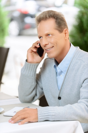blissful: Nice to hear you. Cheerful blissful adult man sitting at the table and taling on mobile phone while feeling joy