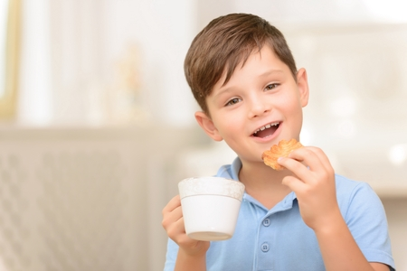 upbeat: Tastes great. Cheerful upbeat little boy eating cookie and drinking tea while evincing joy Stock Photo
