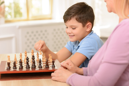 jugando ajedrez: Participa en el juego. Niza niño concentrada sentado en la mesa y jugando al ajedrez con su abuela Foto de archivo