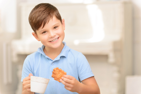 vivacious: Nice meal. Nice vivacious little boy holding cup and drinking tea while eating cookies