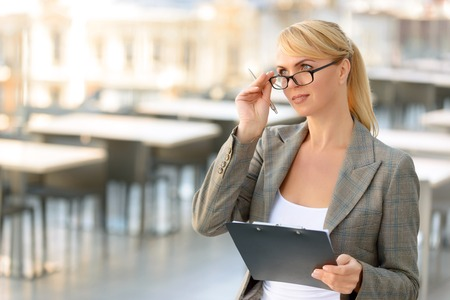 looking aside: Busy worker. Pleasant positive businesswoman holding folder with pen and touching her glasses while looking aside