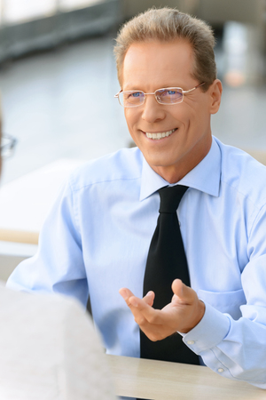 brisk: Like it. Cheerful vivacious businessman sitting at the table and expressing positivity while having brisk conversation with his colleague Stock Photo
