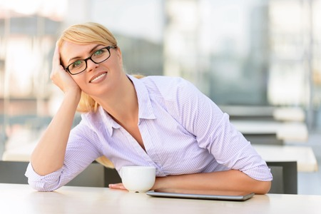 upbeat: Time to relax. Cheerful upbeat charming businesswoman leaning on her hand and drinking tea while sitting at the table